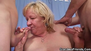 Busty blonde grandma sucks and rides two cocks