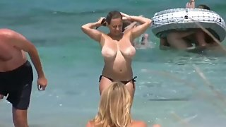 Busty mature MILF walking on the public beach with no bra